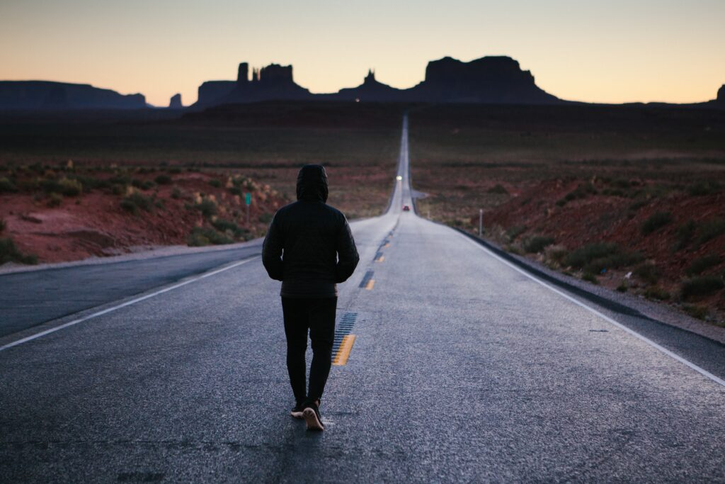 Person in jacket walking empty road in desert