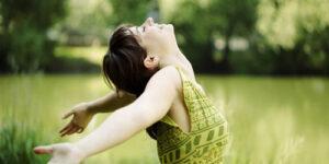 Woman in field feeling happy