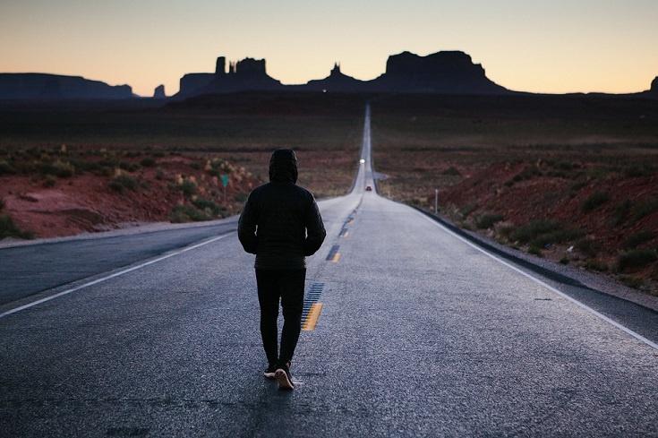 Person in jacket walking down road in desert