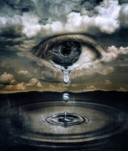 Drawn eye in sky with tear dropping into lake