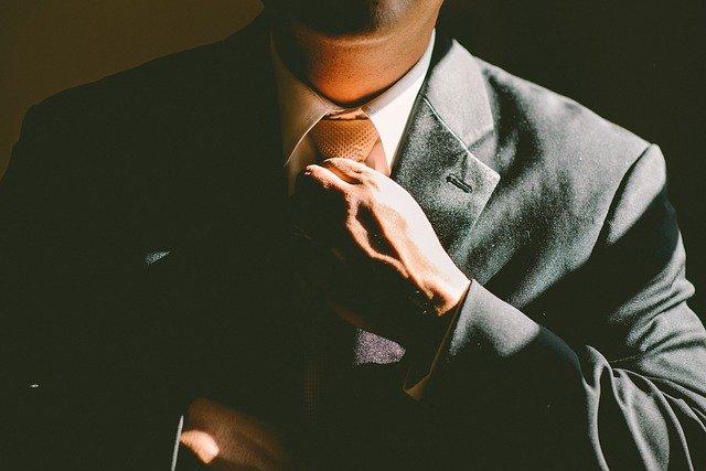 Man in suit straightening tie